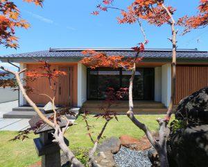ピクチャーウィンドウから庭を眺める平屋の家